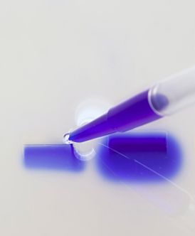 closeup of the tip of a pipette delivering a drop of solution